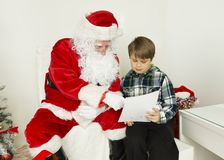 Santa Claus and a boy are reading from a paper. In the center of this horizontal image are Santa Claus and a boy. Boy is wearing dark and light green shirt with Stock Photography