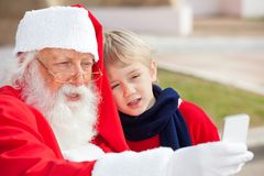 Santa Claus And Boy Taking Selfportrait Through Royalty Free Stock Image