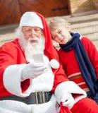 Santa Claus And Boy Taking Selfportrait Through Royalty Free Stock Photos