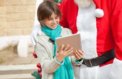 Santa Claus And Boy Using Digital Tablet Stock Photo