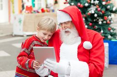 Santa Claus And Boy Using Digital Tablet Royalty Free Stock Photography