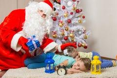Santa Claus bracht giften, klopjes op hoofd van slaapkinderen, en onderzocht het kader Royalty-vrije Stock Foto