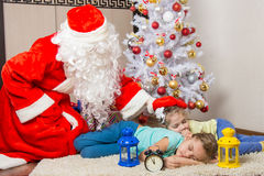 Santa Claus brought gifts and pats on head of sleeping children Stock Images