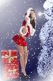 Santa claus brunette kissing a snowman Royalty Free Stock Photos