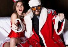 Santa Claus brutal con la mujer atractiva de la enfermera de sexo femenino en el traje del carnaval, conduciendo en el sofá tiene Imagenes de archivo