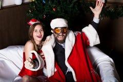 Santa Claus brutal con la mujer atractiva de la enfermera de sexo femenino en el traje del carnaval, conduciendo en el sofá tiene foto de archivo libre de regalías