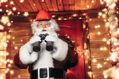 Santa claus in helmet. Santa Claus is a builder. House of Santa Claus. Portrait of Santa Claus in a helmet on his head standing near his decorated house and stock images