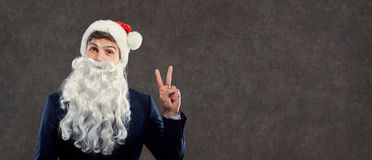 Santa Claus in business suit showing thumbs up symbol of victory Royalty Free Stock Photography