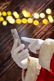 Santa claus is calling. Santa claus`s hands holding a smartphone to call or write a message on wooden background royalty free stock photo