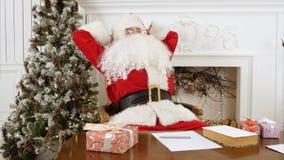 Santa Claus cansada que despierta de una siesta para continuar preparando presentes Imagen de archivo libre de regalías