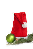 Santa Claus cap and green ball on white Royalty Free Stock Images