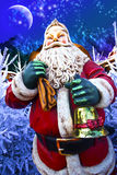 Santa claus card. Statue of santa claus outside holding a bag of gifts and a bell, surrounded of christmas tree, with a north pole blue mountains and blue shiny Royalty Free Stock Photo