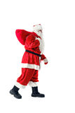 Santa Claus carries a bag with gifts. Royalty Free Stock Images