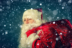 Santa Claus carries gifts. Stock Photos