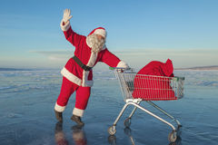 Santa Claus carries a shopping cart with gifts in a sack Stock Photo