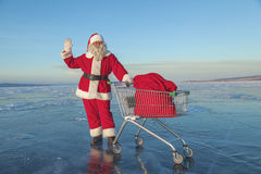 Santa Claus carries a shopping cart with gifts in a sack Royalty Free Stock Photography