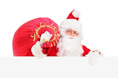 Santa Claus carrying a bag behind a billboard. Santa Claus carrying a bag and posing behind a blank billboard  on white background Stock Images