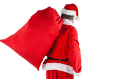Santa claus carrying bag full of gifts Royalty Free Stock Photos