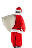 Santa claus carrying bag full of gifts Stock Images