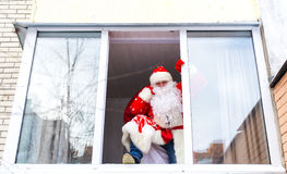 Santa Claus carrying a bag of gifts and climbs into the room through the window. Royalty Free Stock Photos