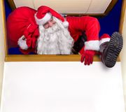 Santa Claus climbs into the window Royalty Free Stock Images