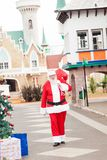 Santa Claus Carrying Bag While Walking In. Full length of Santa Claus carrying bag while walking in courtyard Royalty Free Stock Images