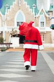 Santa Claus Carrying Bag While Walking In. Rear view of Santa Claus carrying bag while walking in courtyard Stock Photography