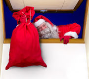 Santa Claus carrying a bag in the window Royalty Free Stock Images
