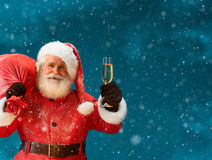 Santa Claus carrying big bag full of gifts with a glass of champagne and looking at camera Stock Photography