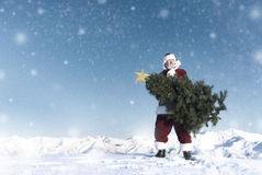 Santa Claus Carrying Christmas Tree auf Schnee-Gebirgskonzept Lizenzfreies Stockfoto