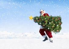 Santa Claus Carrying Christmas Tree på snö Royaltyfri Bild