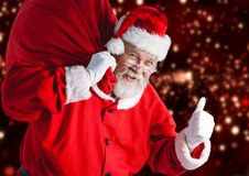 Santa claus carrying gift bag showing thumbs up sign Stock Photo