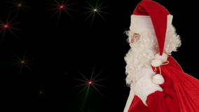 Santa Claus carrying his bag, is looking at the camera and sends a kiss with golden stars, stock footage Stock Photos