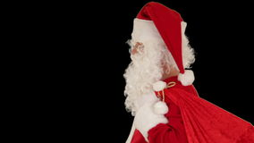 Santa Claus carrying his bag, looks at the camera sends a blow kiss and wave, black, stock footage