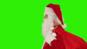 Santa Claus carrying his bag, looks at the camera and winks, Green Screen, stock footage
