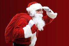 Santa Claus carrying huge red sack with presents Royalty Free Stock Image