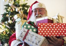 Santa Claus carrying a lot of Christmas presents Royalty Free Stock Photos