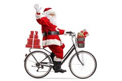 Santa Claus carrying presents on a bicycle and waving. Full length shot of Santa Claus carrying presents on a bicycle and waving  on white background royalty free stock photos