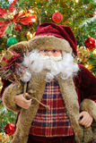 Santa Claus carrying a sack bag with Christmas tree background Stock Photo