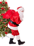 Santa claus  carrying sack by christmas tree. Royalty Free Stock Photography