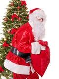 Santa claus  carrying sack by christmas tree. Stock Photos