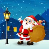 Santa claus carrying sack full of gifts with snowfall falling at night background Royalty Free Stock Images