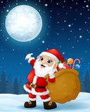 Santa Claus carrying sack full of gifts in the winter night background Stock Images