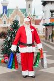 Santa Claus Carrying Shopping Bags In Courtyard Stock Photo