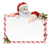 Santa Claus Cartoon Sign. With Santa peeking over a sign that is decorated with Christmas Holly Royalty Free Stock Photos