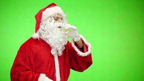 Santa claus celebrating christmas with champagne glass isolated on green. slow motion