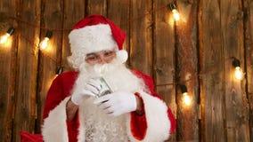 Santa Claus che conta i suoi soldi e che mostra trucco di scomparsa dei soldi stock footage