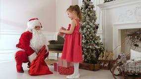 Santa Claus che dà i presente ad una bambina graziosa e che la abbraccia video d archivio