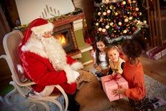 Santa Claus che dà un presente ad una piccola ragazza sveglia davanti alla h Fotografia Stock Libera da Diritti