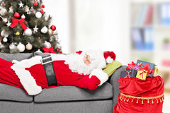 Santa Claus che dorme da un albero di Natale a casa Immagini Stock Libere da Diritti